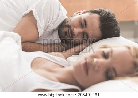 Portrait of calm young man sleeping on bed next to his wife. Peace and comfort concept