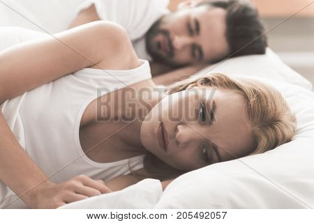Portrait of stressful young woman thinking about her marriage troubles. She is lying on bed while turning back to man. Family problems concept