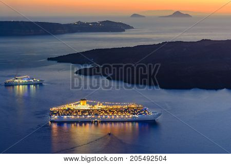 Ship sailing Santorini island, Greece at sunset. Aegean Sea in the town of Oia in the Cyclades off the coast of mainland Greece