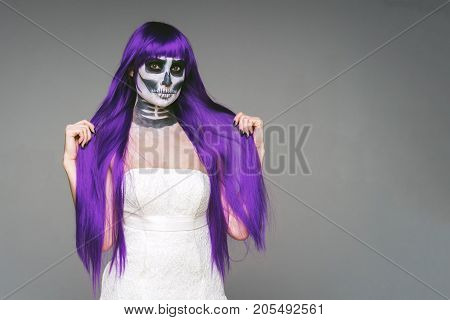 Portrait of woman with terrifying halloween skeleton makeup and purple wig (hair) and wedding dress over gray background looks at the camera