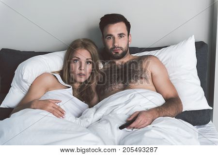 Portrait of married young couple watching tv with excitement. They are lying in bed at home