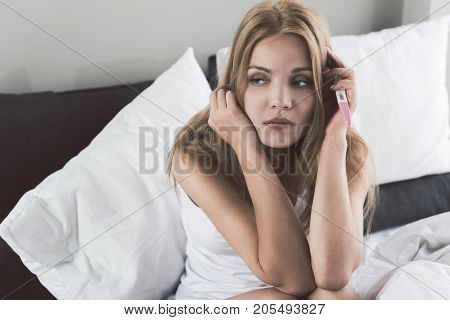 Portrait of depressed young woman holding pregnancy test stick. She is sitting on bed and looking aside with despair. Copy space