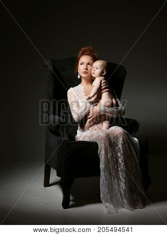 Young mother woman sitting on retro chair holding naked her lovely infant child baby girl on dark background
