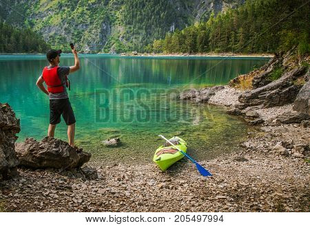 Callphone Signal Search. Kayaker with Smartphone on the Edge of Scenic Lake Looking For Better Phone Signal.