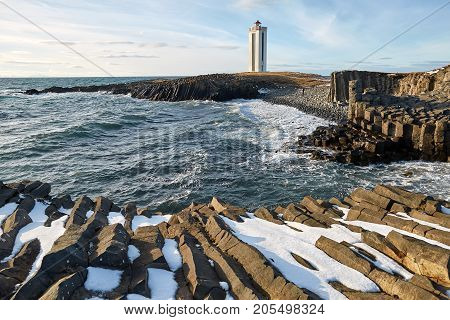 Light lighthouse on the promontory in Iceland on the background of the blue sky with clouds. In front of it there is a rocky shore with remains of snow and a stormy sea. Sun is shining. Horizontal.