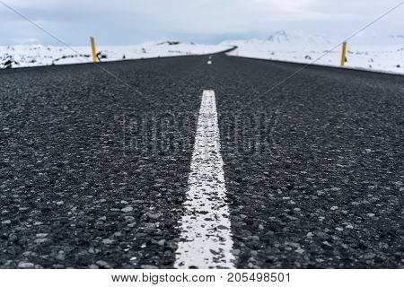 Route with orange roadside pillars between the snow fields and snow mountains on the background of the cloudy sky in Iceland. Closeup. Horizontal.