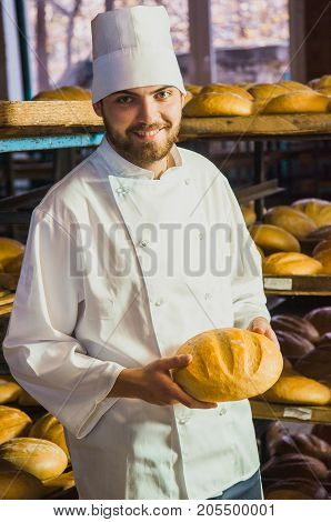 Baker. A Young Handsome Baker Working On A Bread Background Holding Bread In His Hands. Industrial P