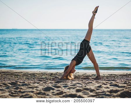 Beautiful young woman practicing morning yoga on sand sea beach. Surya Namaskar - Sun Greetings.