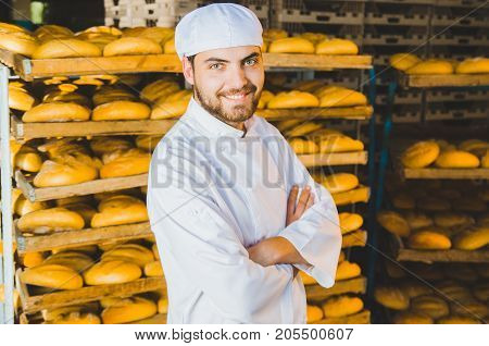Baker. Bakery. A Young Handsome Worker At A Bakery On The Background Of A Rack With Ready-made Bread