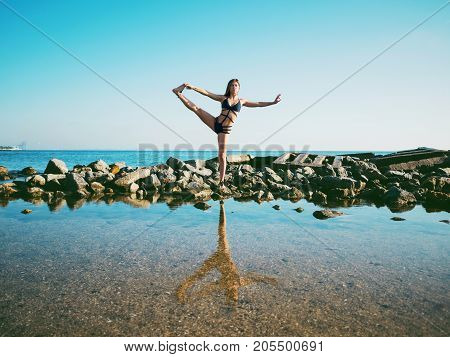 Young caucasian woman in swimsuit practicing yoga in sea water, lake or river. Beautiful reflection. Complex asanas, balance. Fitness, sport, yoga and healthy lifestyle concept.