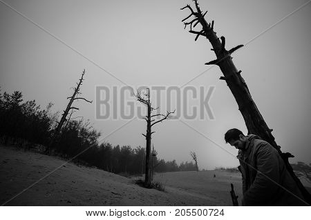 Man with the hung head has leaned the elbows on a dead tree.