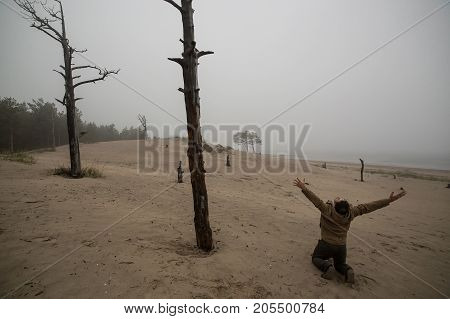 Depressed Man n Has on a Lap Raised Hands Up Against the Background of Dead Trees.