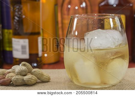 whiskey glass with ice in front of bottles, peanuts on the table