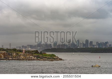 Sydney Australia - March 21 2017: South Head cliffs and park with short Hornby lighthouse up front backed by Sydney skyline under foggy covered cloudscape. Small boat and buoys.