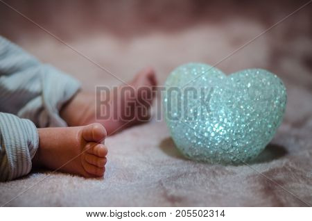 Newborn baby feet in bed close up. Happy Family concept. Beautiful conceptual image of Maternity. Useful as greeting card. Selective focus
