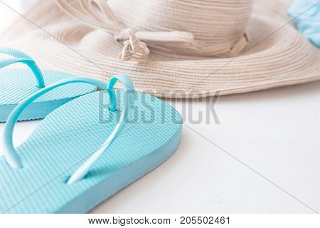 Elegant Women Straw Sun Hat with Bow Blue Beach Flip Flops on White Background Seaside Vacation Relaxation Minimalist Style Poster Template Copy Space