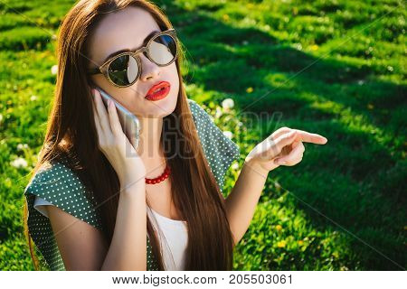 Business woman talking on the phone and pointing a finger at the park