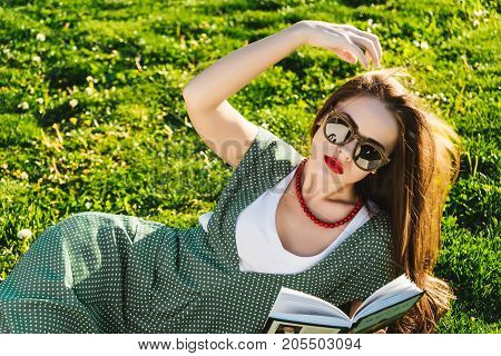 Reading woman on grass.Preparing student in park,sun glasses