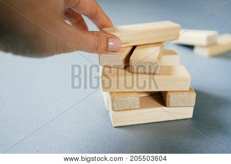 The hand holds a wood briquettes board game