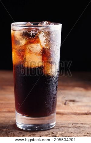 Close Up On A Cold Refreshing Soft Drink With Ice On A Dark Wooden Background