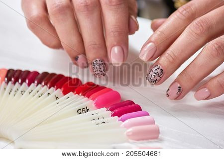 Beautiful female fingers with beige nails. Nude manicure with black lace on womans hands, nails samples. Nails and hands care.