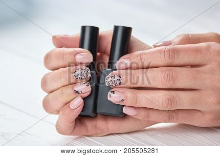 Bottles of nails polish in female hands. Womans hands with warm beige manicure holding two containers of nail varnish. Choice the design and color of nails.