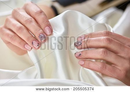 White silk in female manicured hands. Young womans hand with fresh manicure holding silk fabric. Concept of tenderness and womanhood.