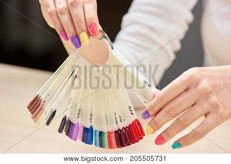 Nails colors samples in female hands. Girl with beautiful summer manicure holding nails colors samples. Big variety of nails colors in professional nail studio.