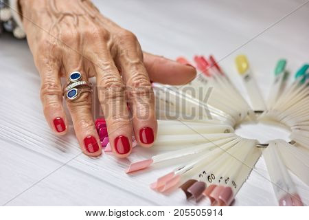 Womans manicured hand with silver ring. Old woman hand with beautiful red manicure wearing luxury ring. Elegant manicure of senior woman.
