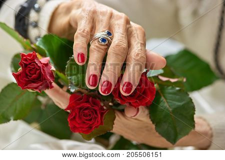 Female hands with manicure and ring. Old woman beautiful manicured hands holding red roses. Female beauty and well-being.