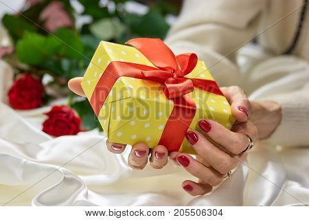 Woman hands holding yellow gift box. Old woman manicured hands holding yellow gift box with red bow. Birthday and celebration concept.