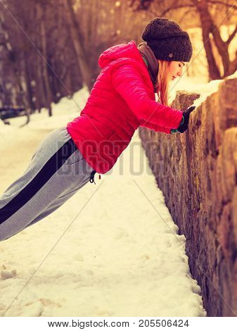Outdoor sport exercising sporty outfit ideas. Woman wearing warm sportswear urban training exercising outside during winter.