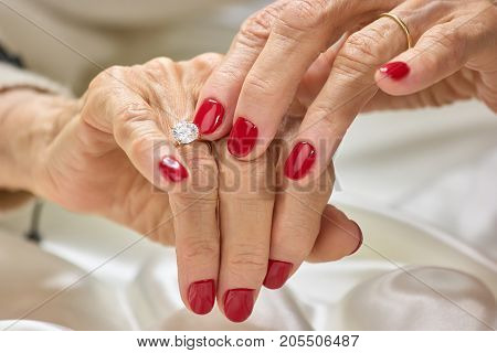 Female manicured hands with diamond. Senior woman hands with red nails and golden ring with diamond. Womans hands with precious jewels.