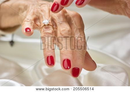 Female finger indicating on diamond. Senior woman with red nails showing her golden ring with precious jewels.