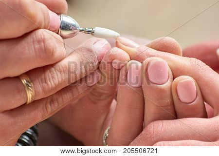 Hardware manicure in beauty salon. Female manicurist remove old gel from clients nails. Nails care and beauty.