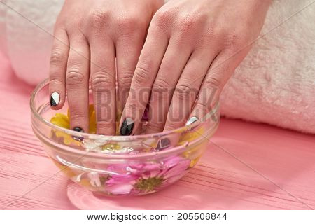 Young woman fingers in aroma bath. Female beautiful hands with manicure receiving spa procedure. Spa treatment for female hands.