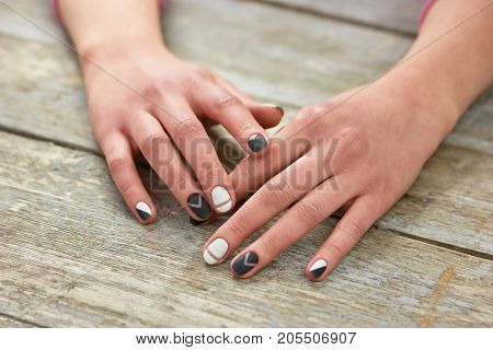 Woman hands with trendy manicure. Female hands with casual manicure on old wooden background. Nail design and spa.