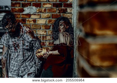 Halloween girl vampire with bloody pumpkin. Woman with red blood and brunette hair. Man or war soldier with wounds. Zombie couple in torn clothes standing on brick wall. Holiday celebration concept.