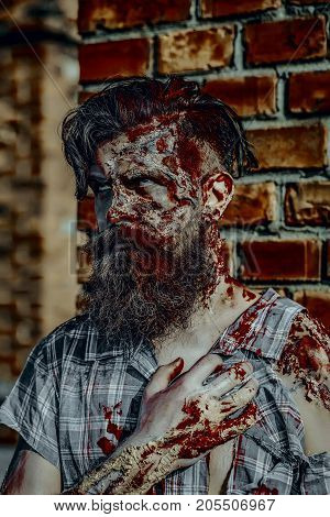 Halloween zombie in torn shirt on brick wall. War soldier with wounds on face. Vampire hipster with red blood outdoors. Holiday celebration concept. Man with bloody beard and hair.
