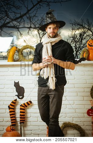 Halloween magic potion concept. Man holding cup at window with autumn trees. Holiday symbols and decorations. Macho wearing witch hat and scarf. Warm and homely atmosphere.