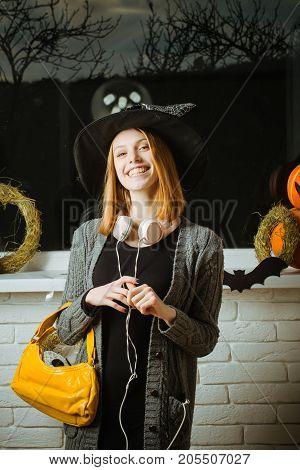 Halloween Girl In Witch Hat With Headphones And Bag Smiling
