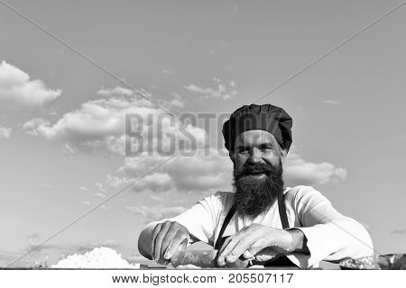 Man cook chef with beard on handsome smiling face in white and red uniform cooking dough sunny outdoor on blue sky background copy space