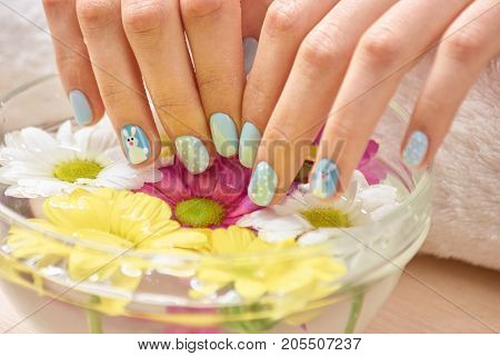 Female hands receiving spa procedure. Woman in beauty salon holding fingers in aroma bath for hands. Close up of female hands with cute winter fingernails soaking in hand bath.