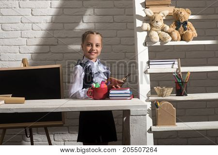 Girl sits at desk with colorful stationery and books. Back to school and homework concept. Kid in school uniform on white brick wall background. Schoolgirl with smile holds open book near bookshelf