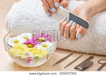 Woman filling nails on towel. Young woman hands in spa salon polishing manicured nails, bath for hands, manicure equipment.