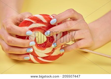 Feminine hands holding bright lollipop. Female hands with stylish winter design nails holding lollipop close up.