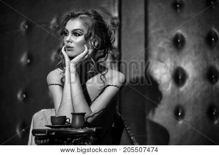 Pretty girl or beautiful woman with stylish makeup and long curly hair wearing pink polka dot dress drinking coffee in cafe on black leather background