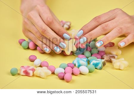 Colorful candies in womans hands. Womans hands with bright manicure taking a colorful candy, yellow background.