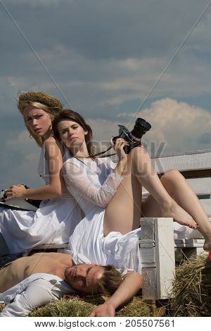 Man or macho lying on hay. Friends relaxing on sunny day on blue sky. Blond girl with vintage typewriter. Brunette woman with camera. Summer vacation concept.