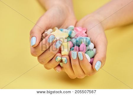 Colorful candies in womans hands. Young woman manicured hands holding colorful candies, yellow background.